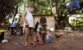 Children play outside their house at a slum in Asuncion, March 31, 2015. Paraguay's government announced that the poverty index rose in 2014 over the previous year, a tendency that goes against the government's official goal of improving the standard of living. REUTERS/Jorge Adorno
